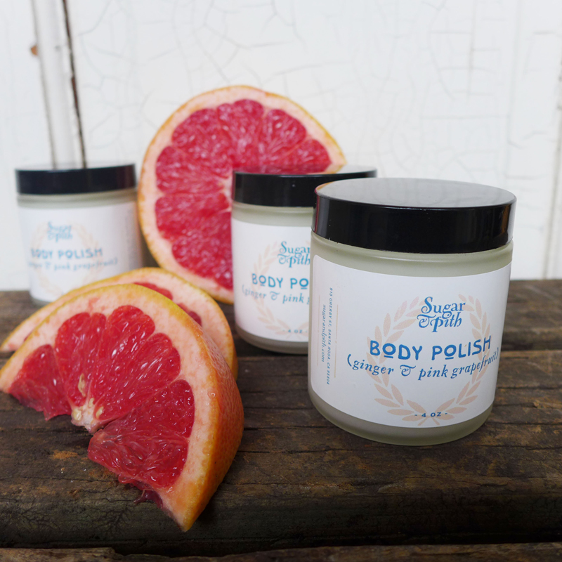 Sugar and Pith ginger and grapefruit body polish, three jars arranged with grapefruit wedges