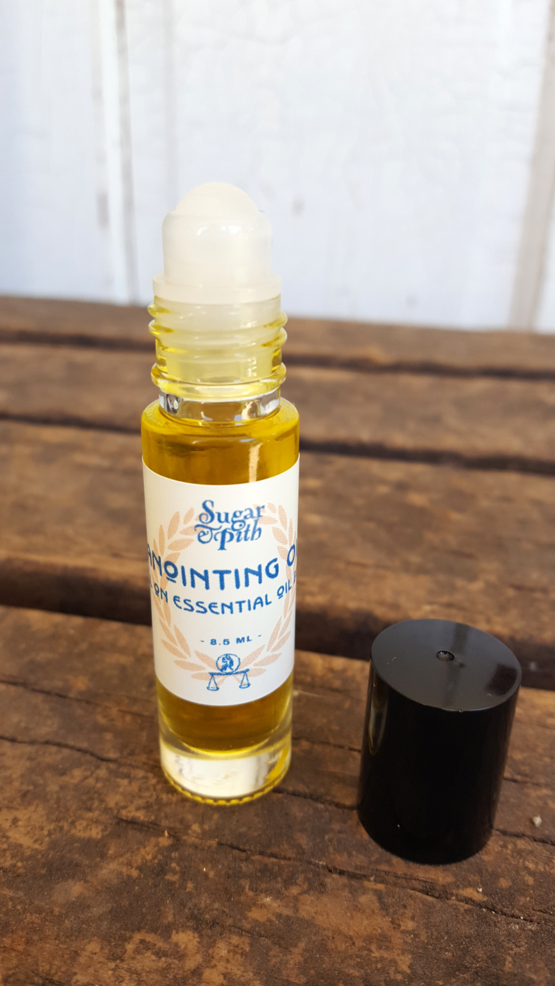 Sugar and Pith, Roll On Anointing Oil, one roll on bottle of Anointing Oil sitting on rustic wood with the lid off