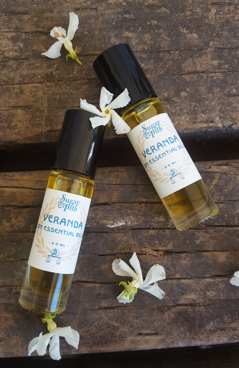 Sugar and Pith, Roll On Veranda, two roll on bottles of Veranda essential oils on a rustic wood table with white jasmine flowers scattered around them.