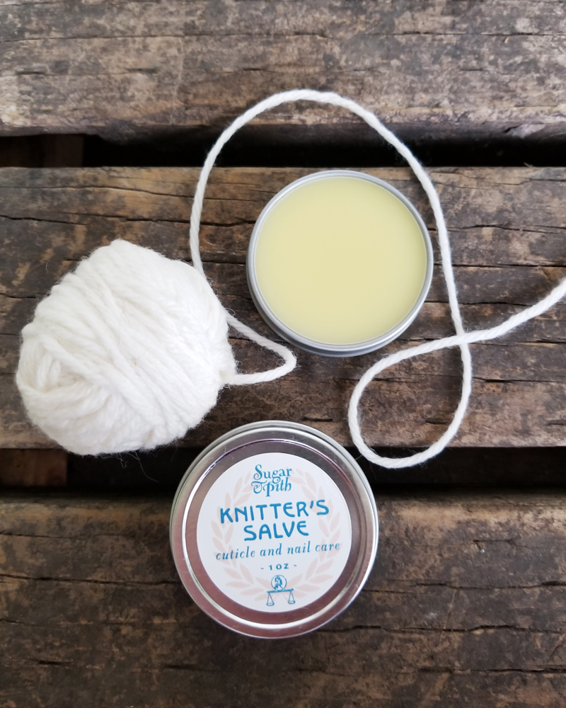 Sugar and Pith, Knitter's Salve, two tins of Knitter's Salve on a rough wood surface with a ball of white yarn unspooling around them